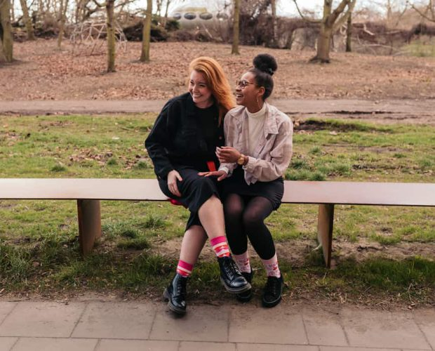 two beautiful women sitting close together on a bench laughing and looking to the left wearing their sisu socks